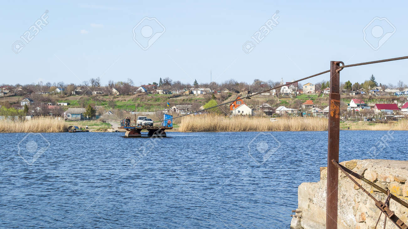Ukraine, Southern Bug River - 2 April 2017: Ferry crossing. The ferry moves with the help of a man's muscular strength. Repels from the steel cable. Such a ferry is unique in Ukraine. Banque d'images - 84621129