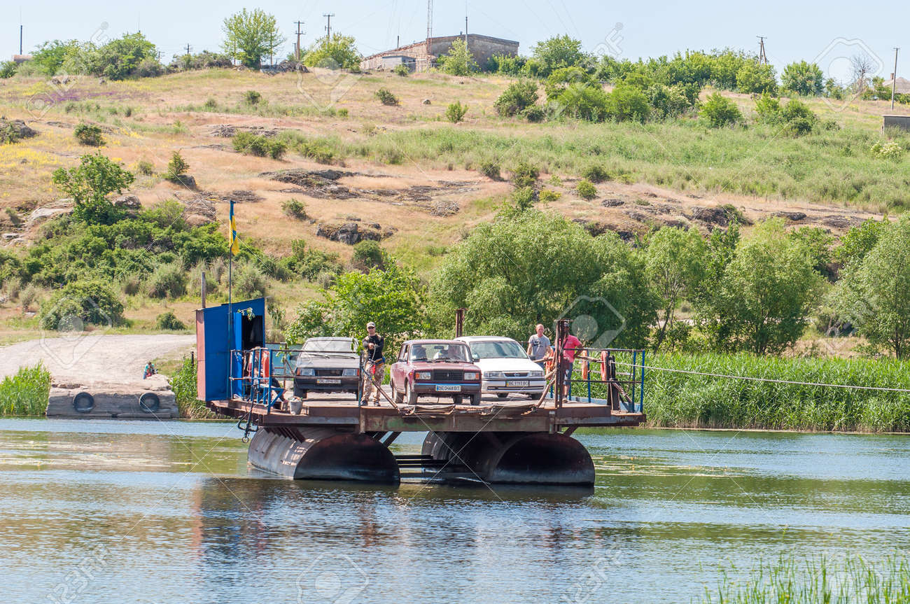 Ukraine, Southern Bug River - 4 June 2017: Ferry crossing. The ferry moves with the help of a man's muscular strength. Repels from the steel cable. Such a ferry is unique in Ukraine. Banque d'images - 84459830