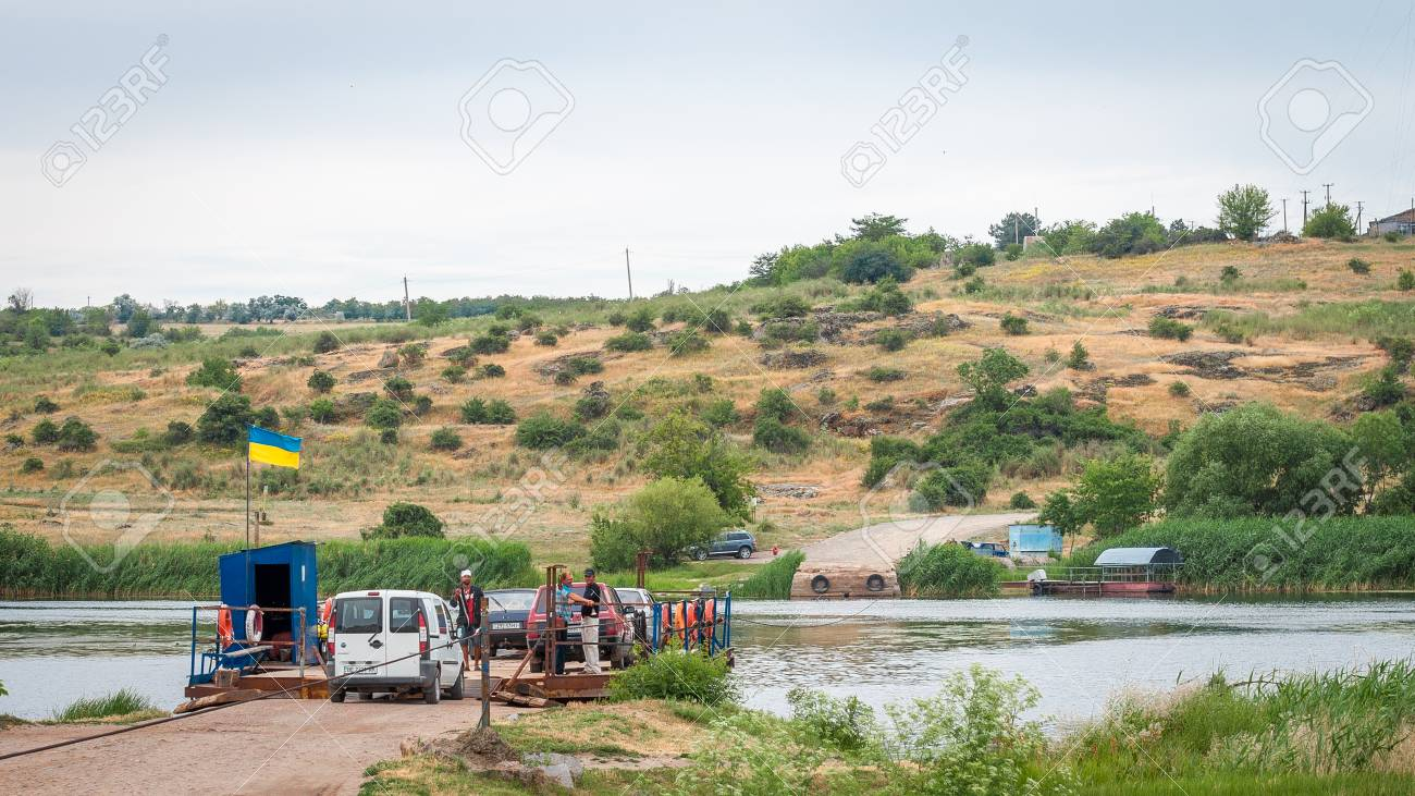 Ukraine, Southern Bug River - 18 June 2017: Ferry crossing. The ferry moves with the help of a man's muscular strength. Repels from the steel cable. Such a ferry is unique in Ukraine. Banque d'images - 84459832