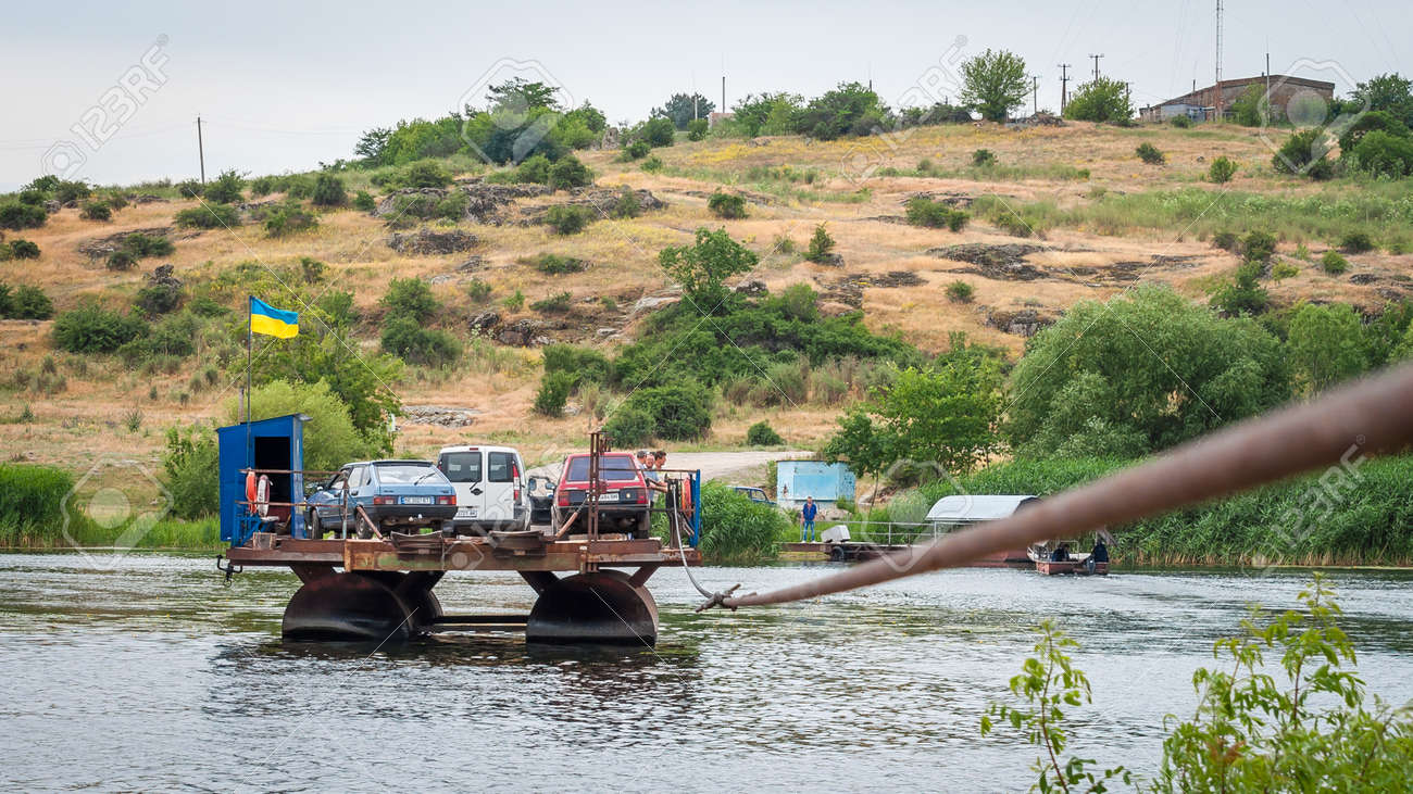 Ukraine, Southern Bug River - 18 June 2017: Ferry crossing. The ferry moves with the help of a man's muscular strength. Repels from the steel cable. Such a ferry is unique in Ukraine. Banque d'images - 84459837