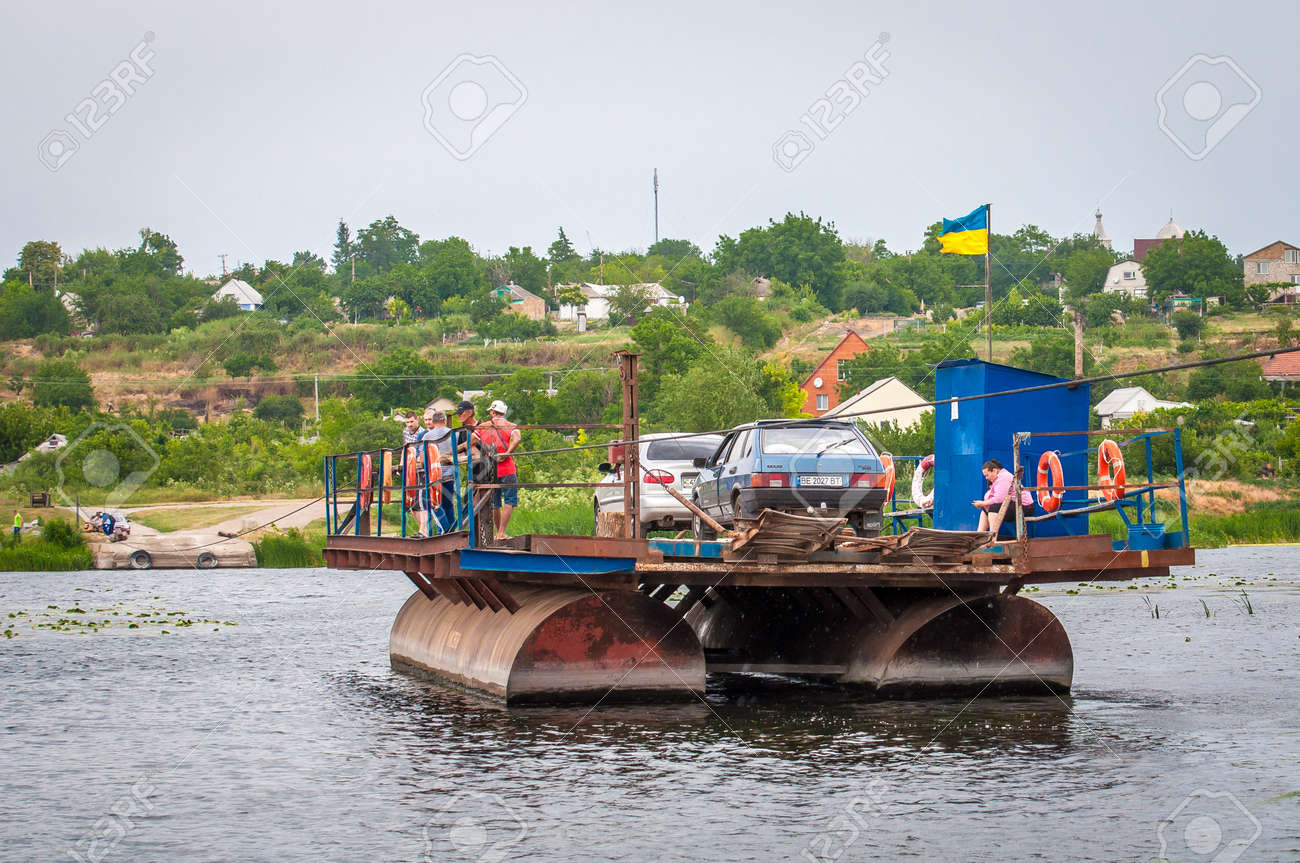 Ukraine, Southern Bug River - 18 June 2017: Ferry crossing. The ferry moves with the help of a man's muscular strength. Repels from the steel cable. Such a ferry is unique in Ukraine. Banque d'images - 84459839