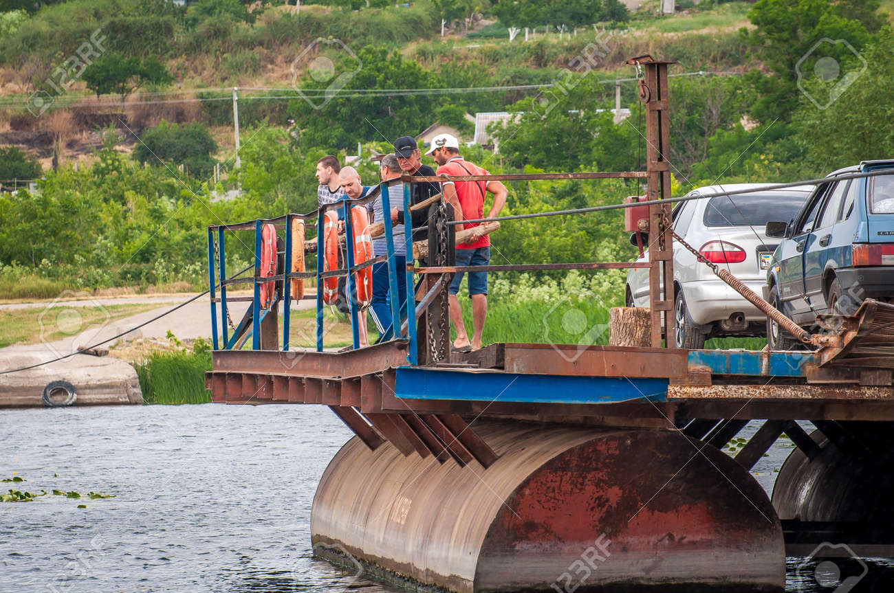 Ukraine, Southern Bug River - 18 June 2017: Ferry crossing. The ferry moves with the help of a man's muscular strength. Repels from the steel cable. Such a ferry is unique in Ukraine. Banque d'images - 84459920