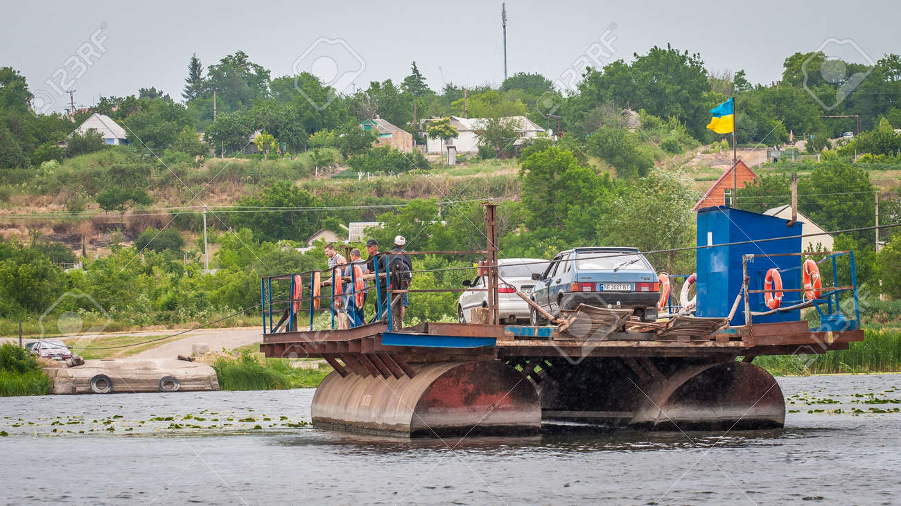 Ukraine, Southern Bug River - 18 June 2017: Ferry crossing. The ferry moves with the help of a man's muscular strength. Repels from the steel cable. Such a ferry is unique in Ukraine. Banque d'images - 84459943