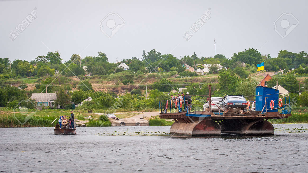 Ukraine, Southern Bug River - 18 June 2017: Ferry crossing. The ferry moves with the help of a man's muscular strength. Repels from the steel cable. Such a ferry is unique in Ukraine. Banque d'images - 84459949