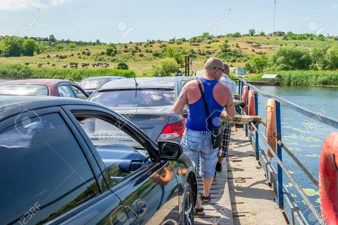 Ukraine, Southern Bug River - 4 June 2017: Ferry crossing. The ferry moves with the help of a man's muscular strength. Repels from the steel cable. Such a ferry is unique in Ukraine. Banque d'images - 84459974