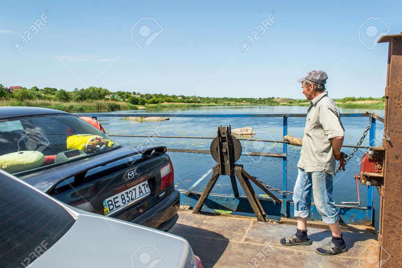 Ukraine, the Southern Bug River - 4 June 2017: crossing. The ferry moves by the muscular strength of man. Repels from the steel cable. The ferryman moves this floating object. Banque d'images - 84459987
