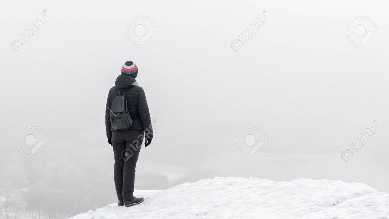 The girl on a frosty winter day is standing on a snow-covered rock and staring into the distance. Fog. Soft focus Banque d'images - 94034329