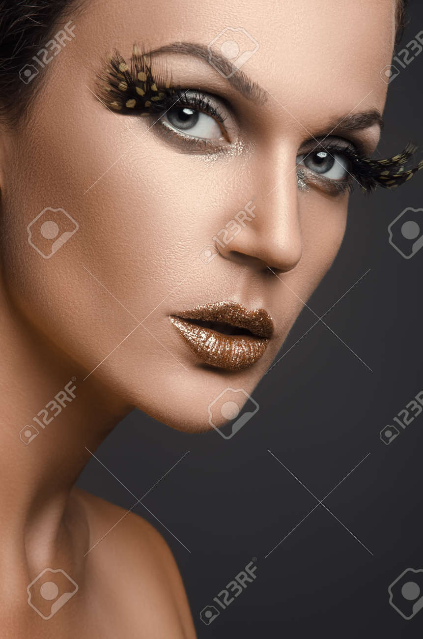 2aa0b20b8b3 Portrait of beautiful woman in studio with big false eyelashes on a dark  background Stock Photo