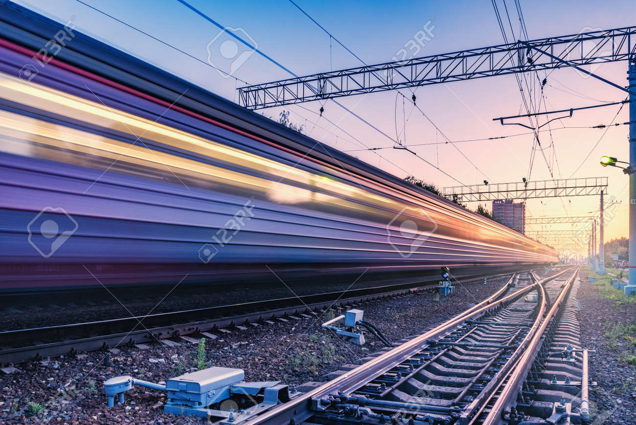 Passenger train moves fast at sunset time. - 131071807