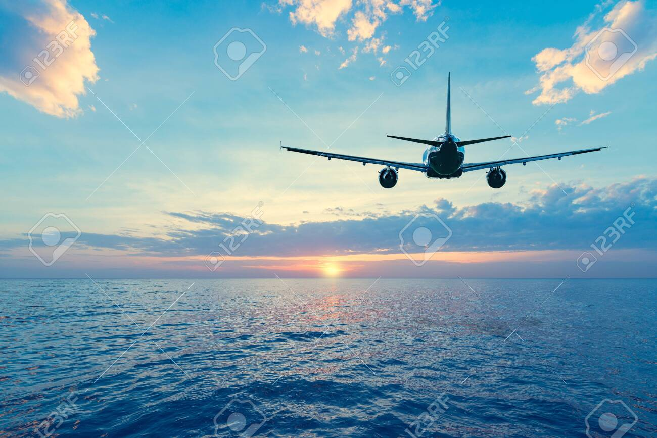 Flying of the passenger plane above the sea surface at sunset time. - 135750744