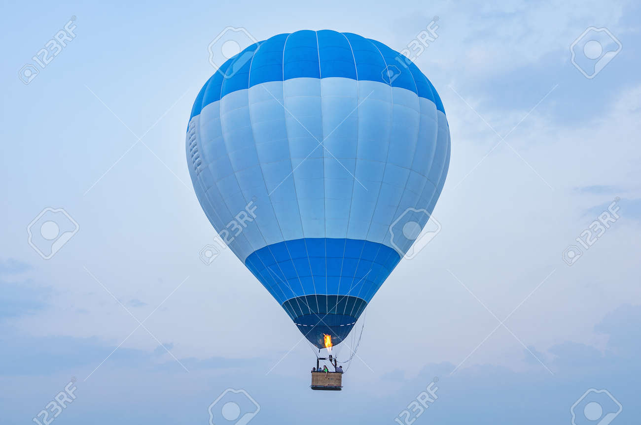 Blue hot air balloon above the land at evening time. - 148540241