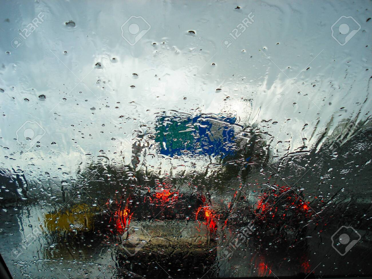 View of road and traffic jams on a rainy day from inside a car with the wet car glass - 125840425