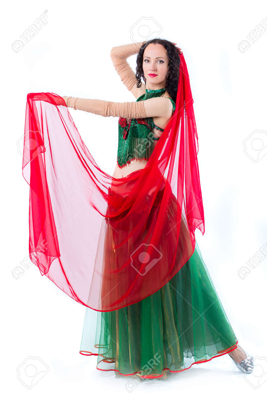 The girl is froze in a dance position. The girl in a green dress and with a red scarf on a photo studio. Isolated on a white background - 146029333