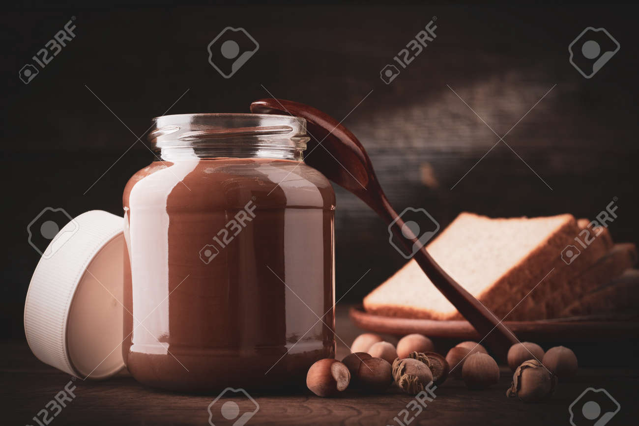 Jar of chocolate-nut pasta with slices of fresh white bread and hazelnuts on wooden background. - 137548501