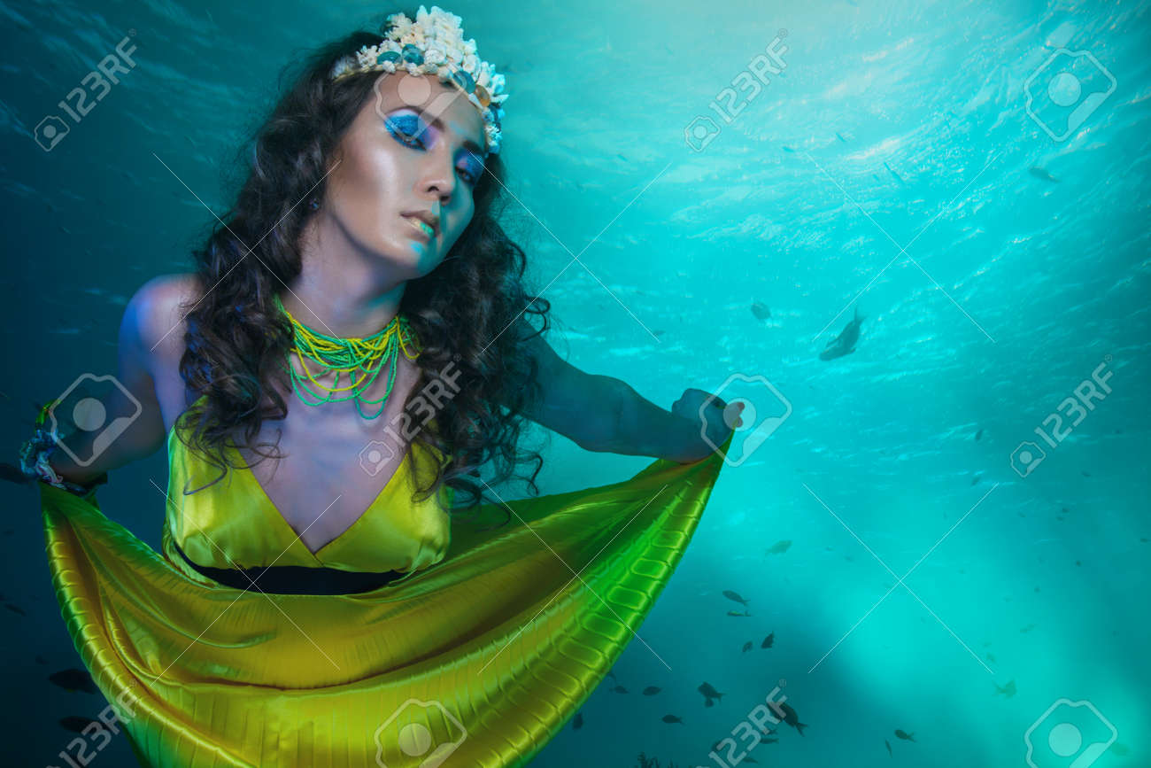 beauty shoot of a woman mermaid in gold dress under the sea with