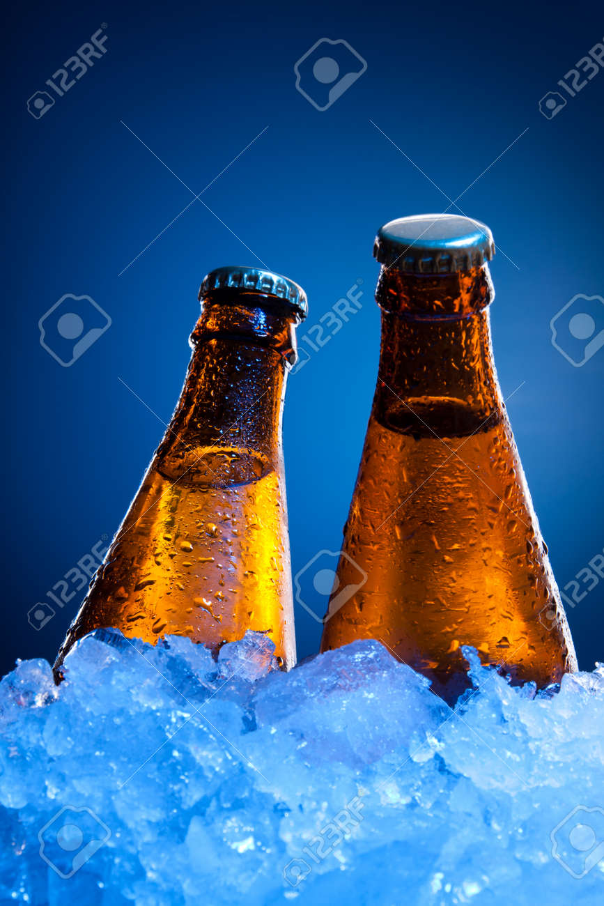 Couple cold beer bottles in ice on blue background Stock Photo - 10142779