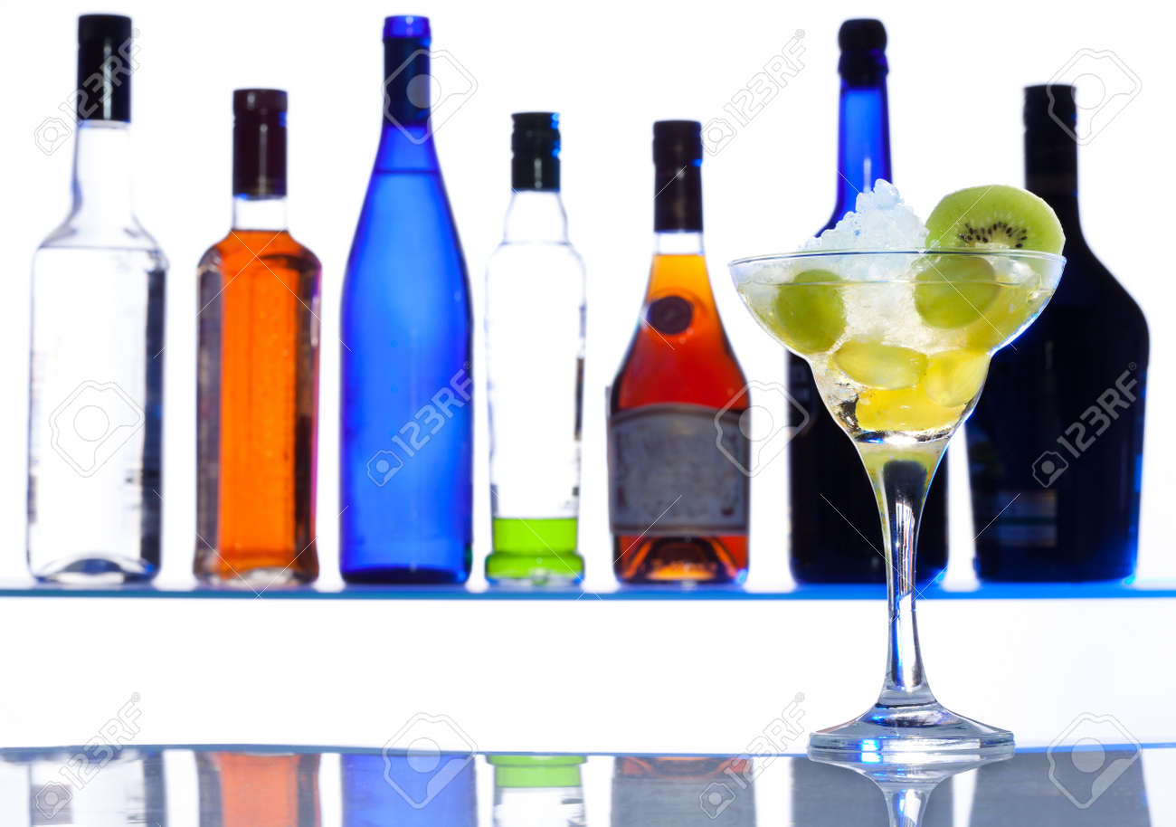 Cocktail glass with drink with bottles on the white bar background Stock Photo - 11730577