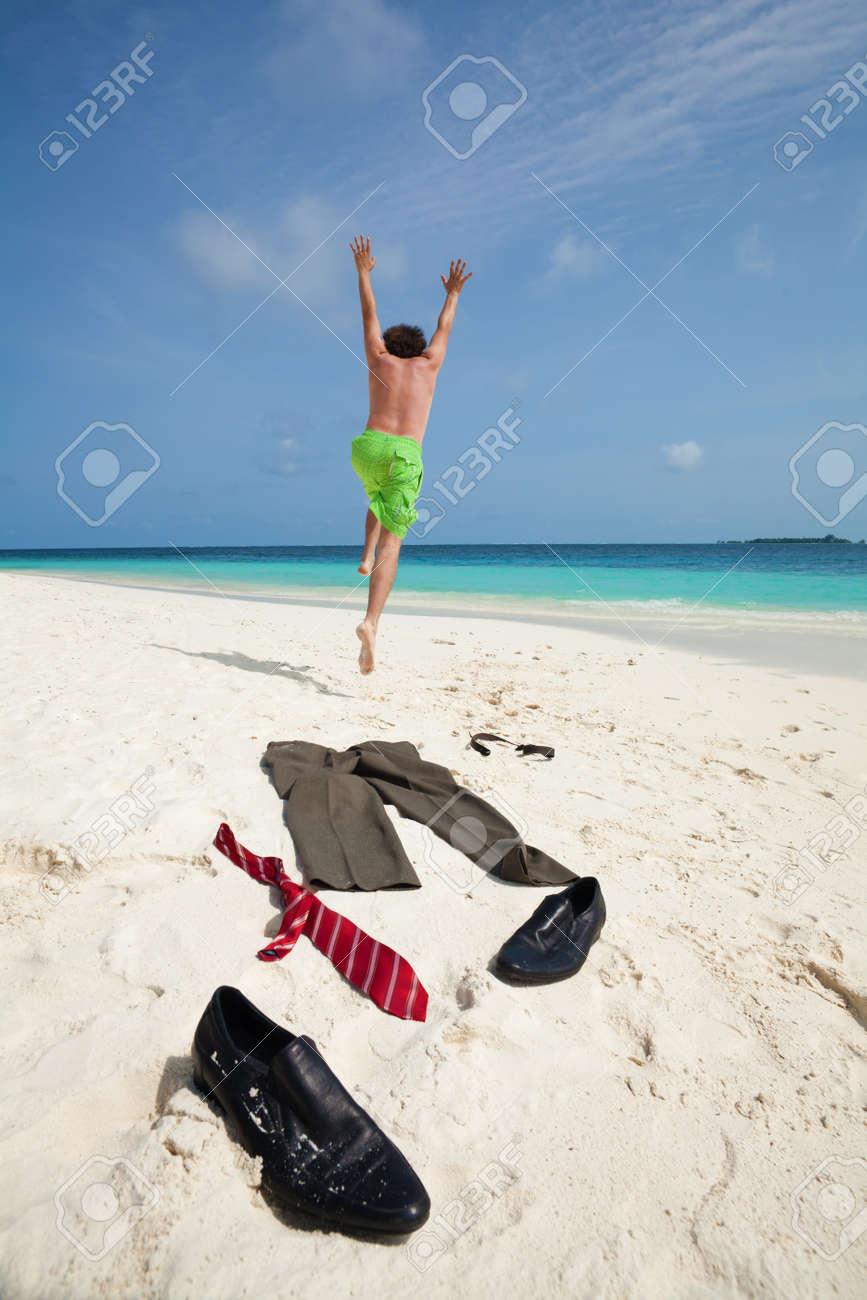 Happy business man running in to ocean to swim with clothes such as boots, tie and pants taken off and laying on the white sand Stock Photo - 11753760