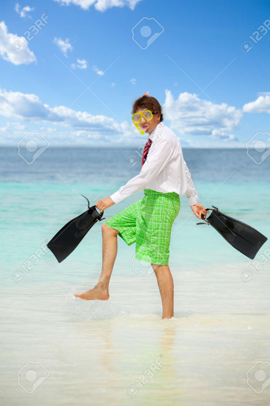 Businessman wearing snoring mask with flippers and wearing formal clothes with red tie entering water on the beach Stock Photo - 11750280