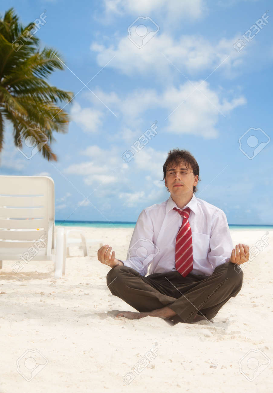 Office worker sitting on the beach an meditating Stock Photo - 11730574