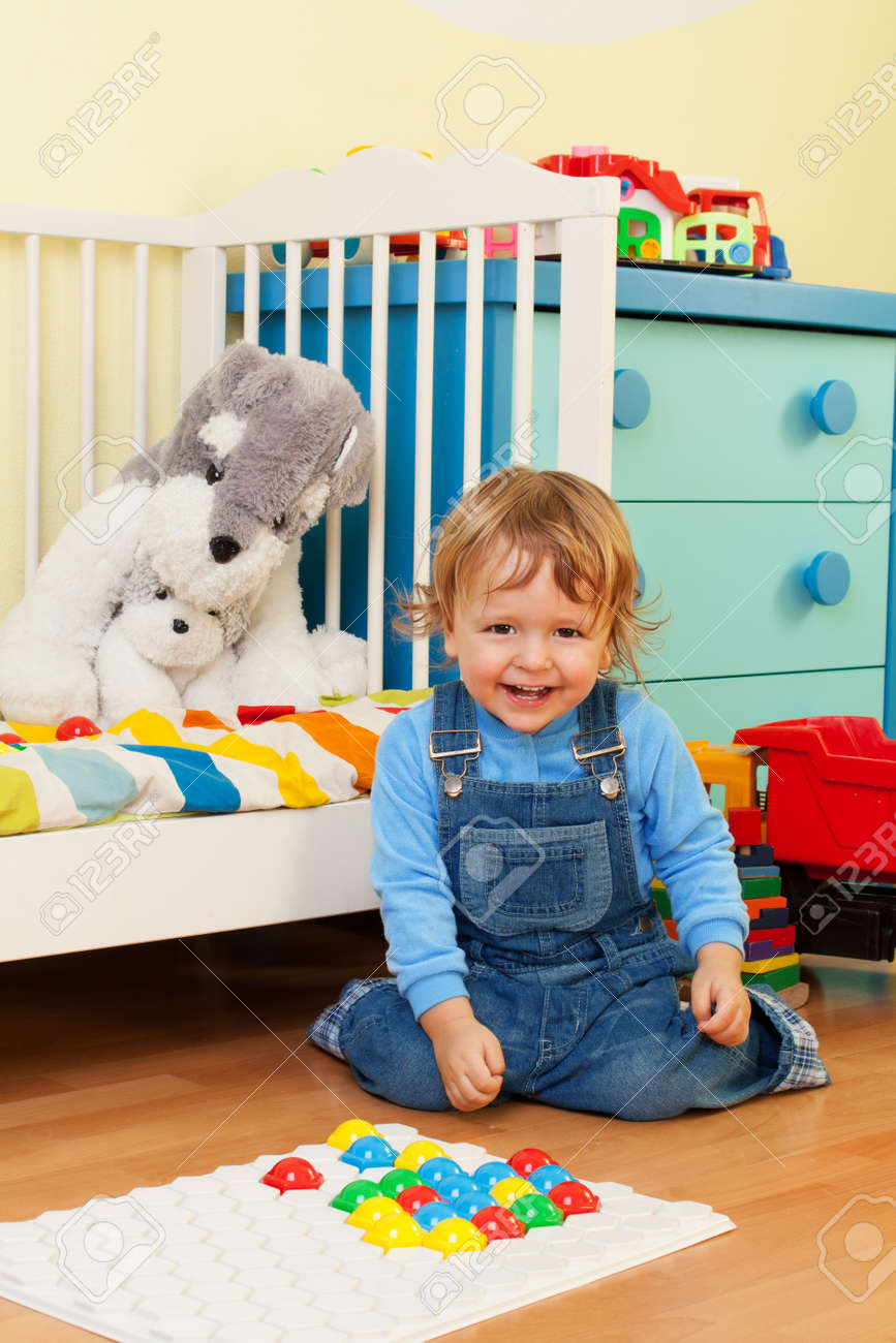 Laughing boy playing with mosaic in kids room Stock Photo - 13948793