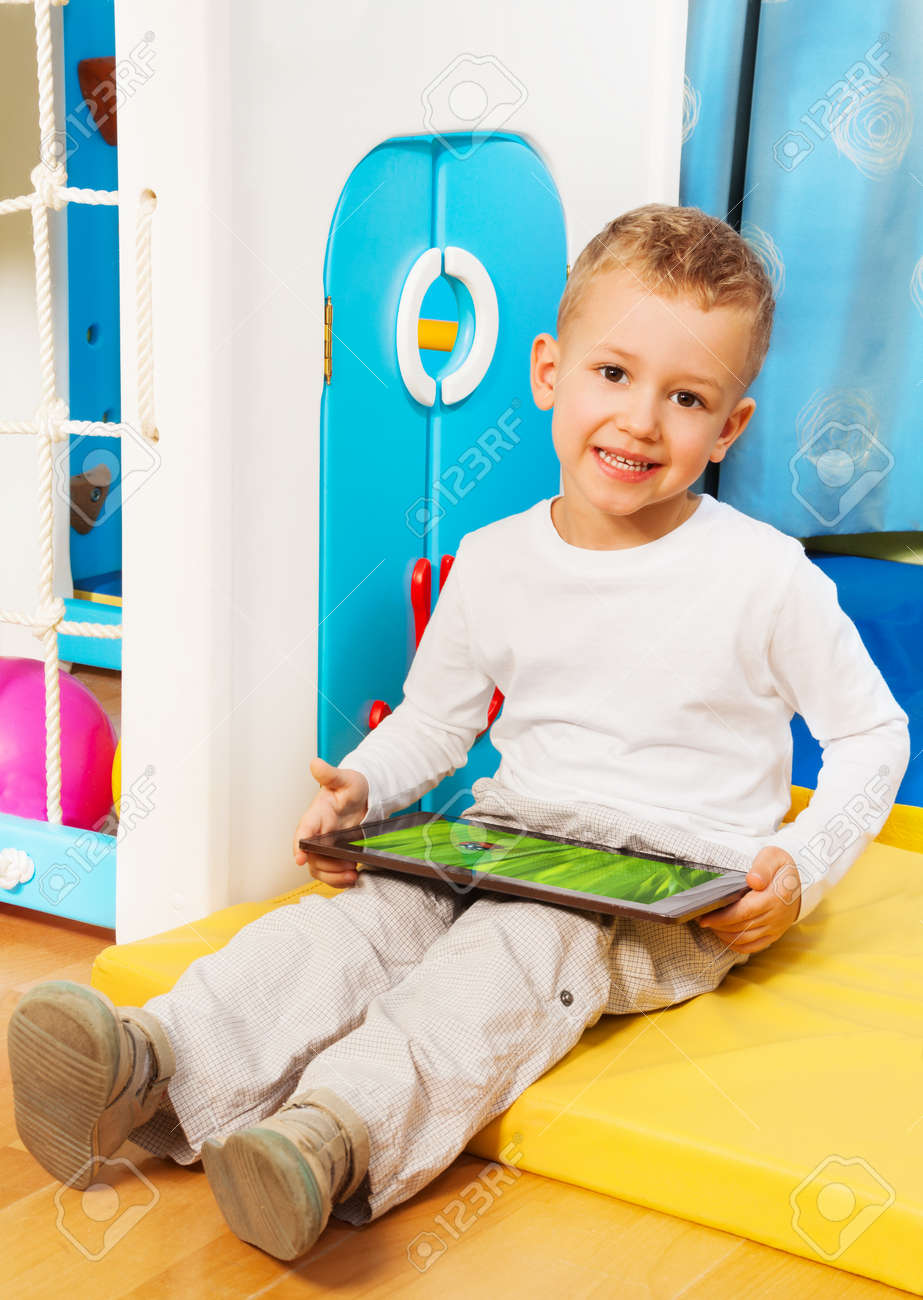 Little five years old smiling blond boy sitting in kids room with tablet computer Stock Photo - 17421802