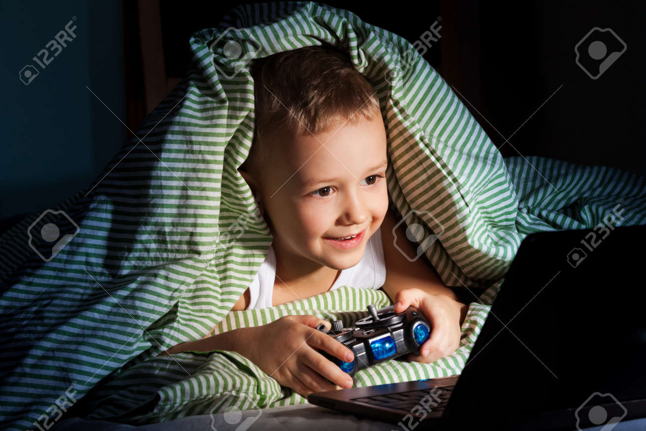 five years old happy kid hiding under blanket playing computer games Stock Photo - 17421891