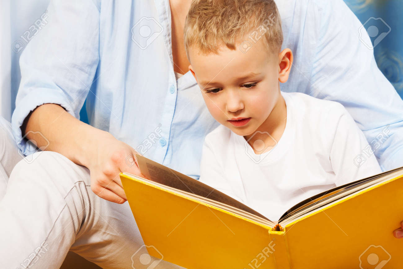 Five years old boy reading a book with his mother Stock Photo - 17421830