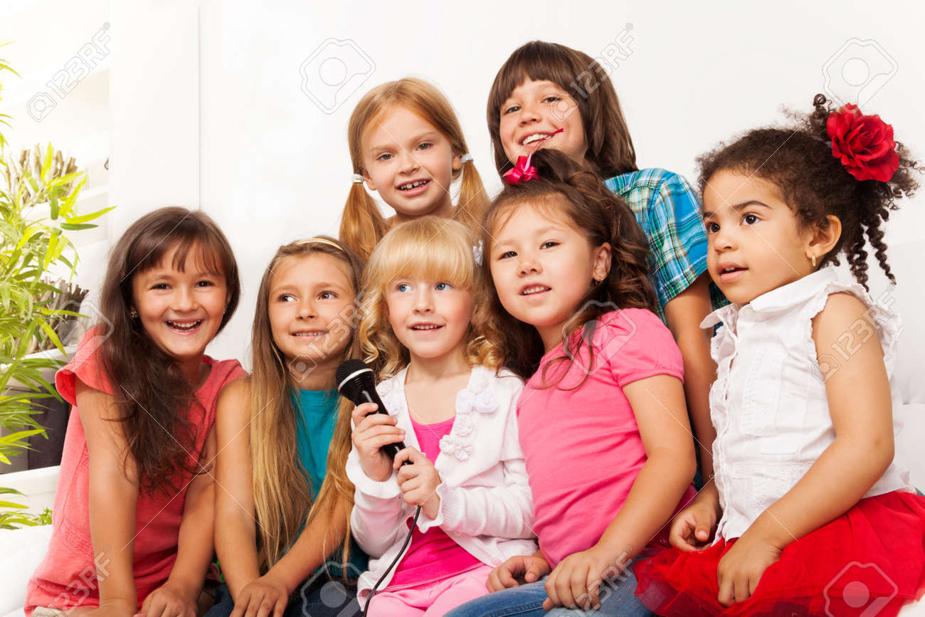large group of five happy little kids boys and girls singing