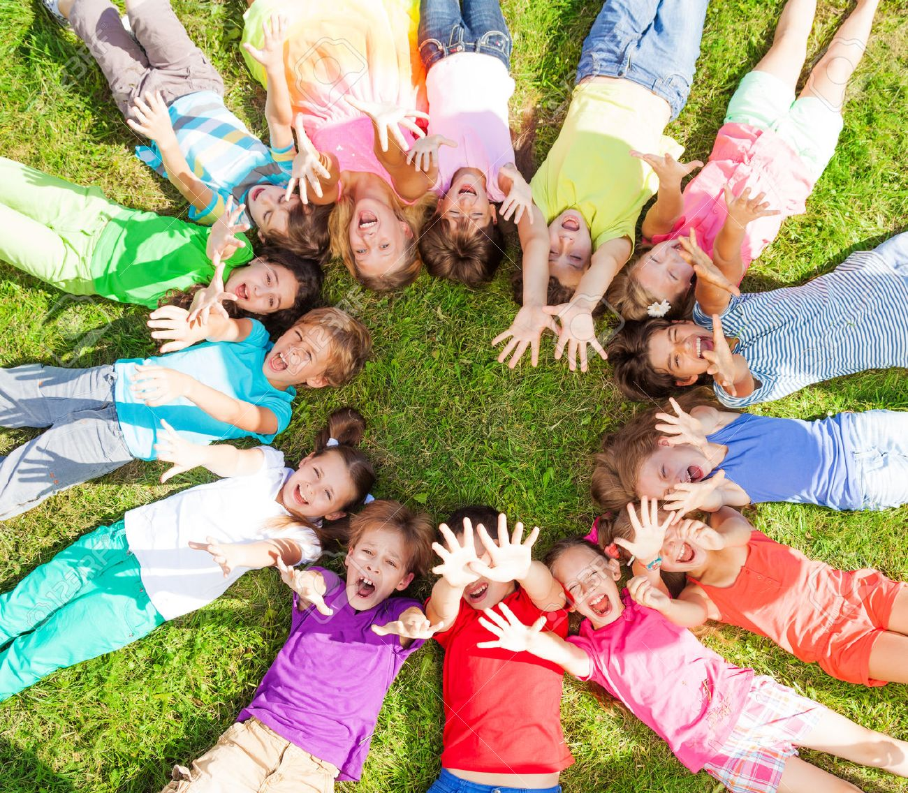14 kids laying in a circle in the grass with happy faces shoot from above lifting hands above Stock Photo - 22404196