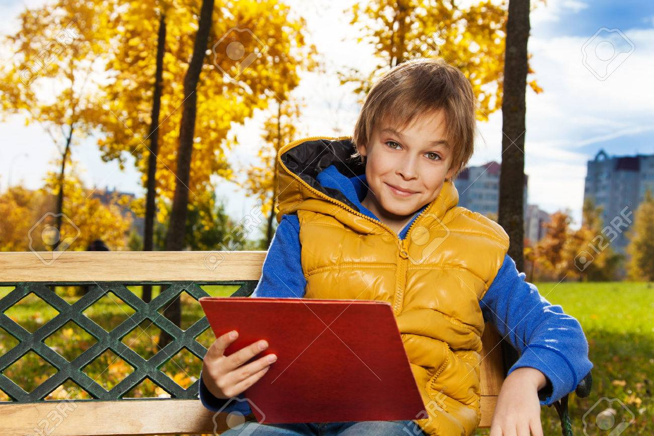 Close portrait of happy 10 years old boy sitting on the bench with rucksack  with backpack 5063d6ccba2bc