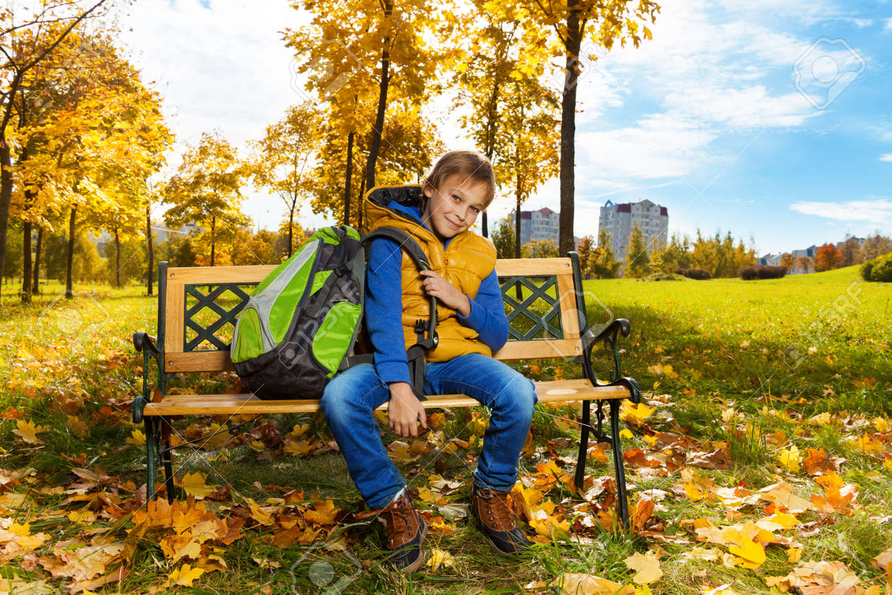 Happy 10 years old boy sitting on the bench with backpack after school with  backpack on 4e6a8447ad58e