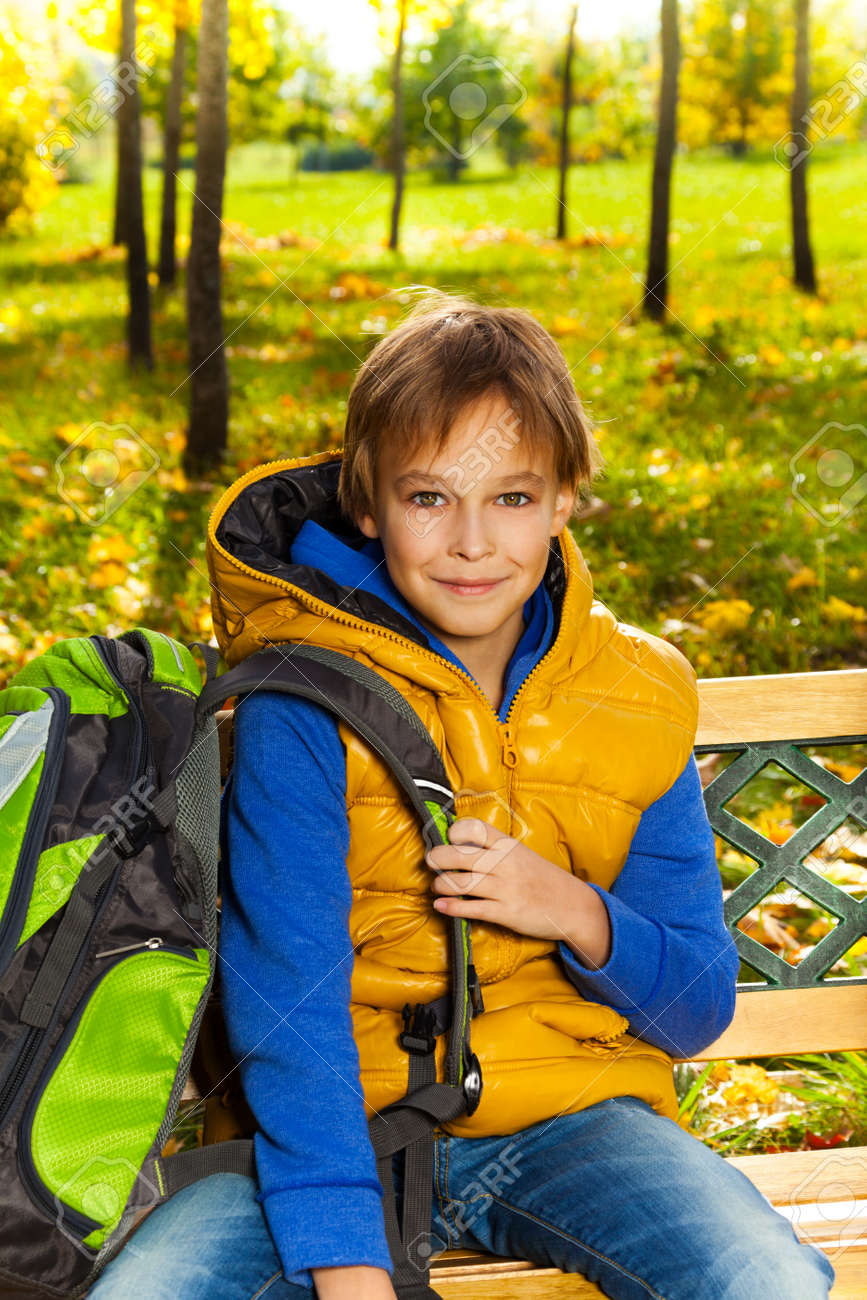 Portrait of happy 10 years old boy sitting on the bench with rucksack with backpack  after 242b7c7e0aa8d