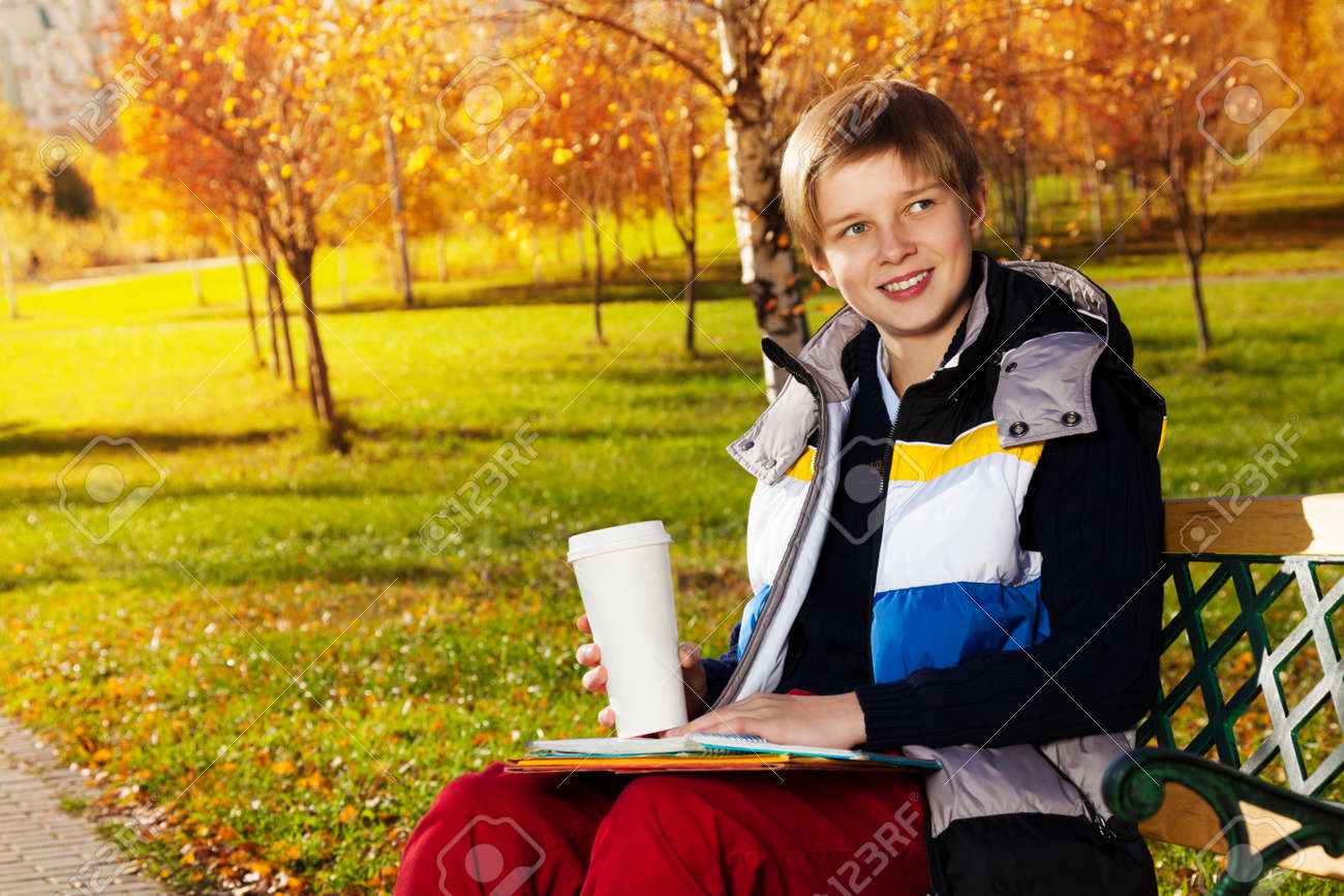 10 years old boy sitting on the bench in autumn park holding books and  coffee smiling d42ace147ee3a