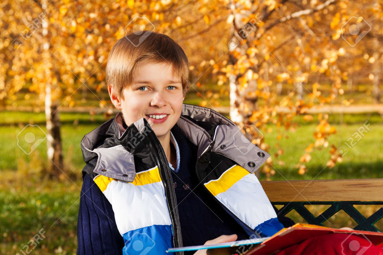Close portrait of 10 years old boy sitting on the bench in autumn park  Stock Photo ffecbe8a07d34