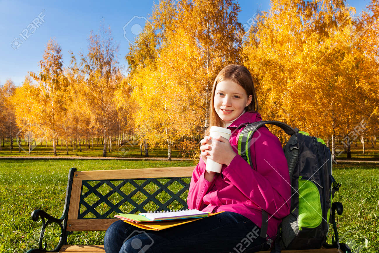 Beautiful teen 14 years old school girl sitting on the bench in autumn park  wearing backpack 0f46eb3decf8a