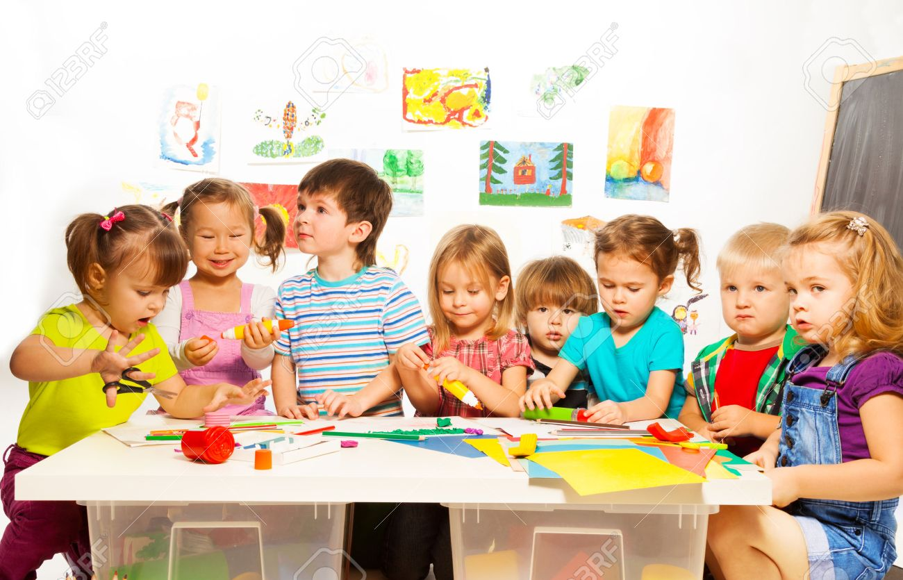 kindergarten large group of little kids painting with pencils and gluing with glue stick on - Little Kids Pictures