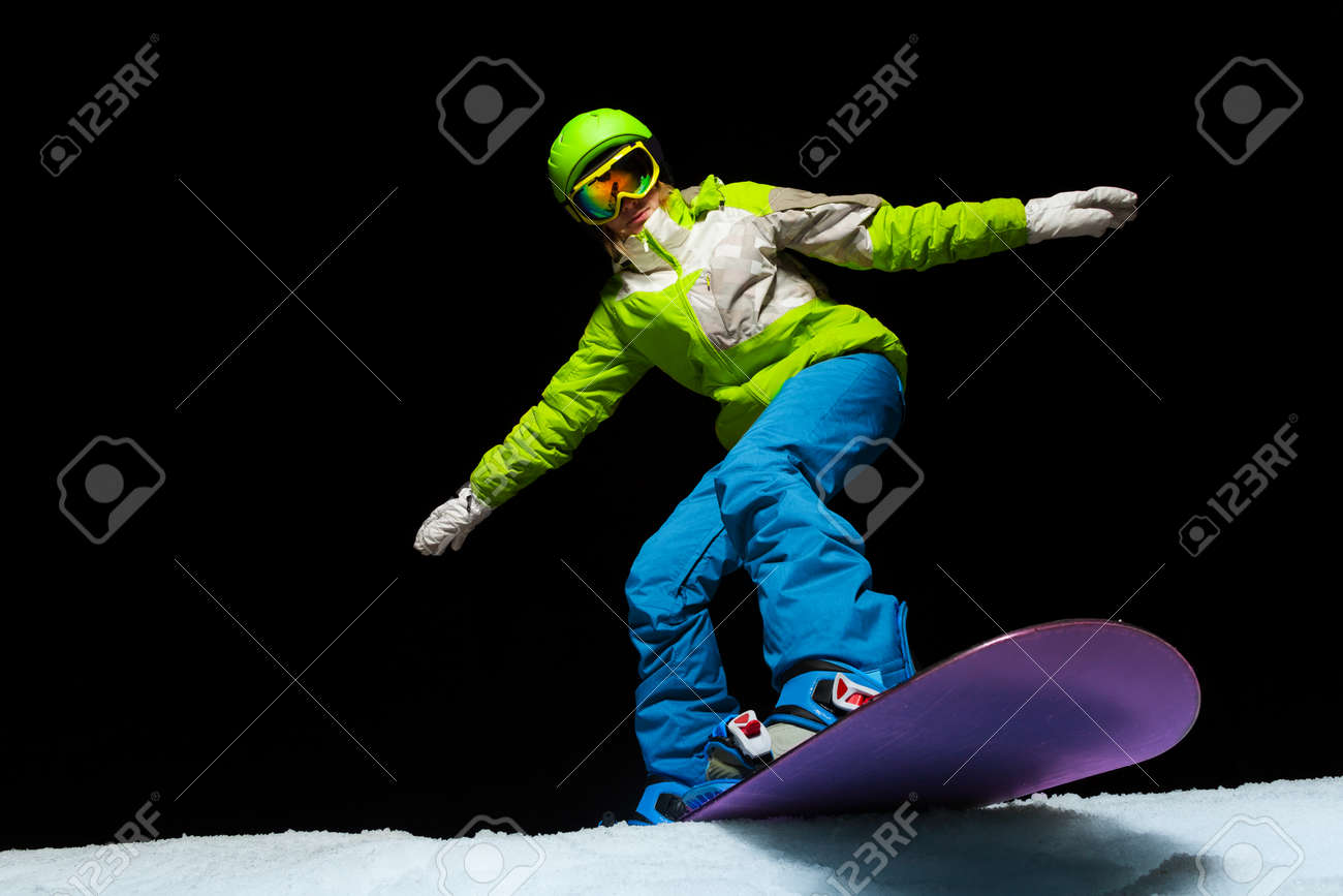 d8af3e2ef46d Stock Photo - Woman wearing ski mask balancing with hands on snowboard and  ready to slide down at night