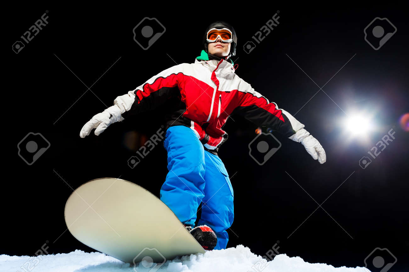 c972333a0bf7 Portrait of young snowboarder wearing ski mask ready to slide from mountain  at night with flash