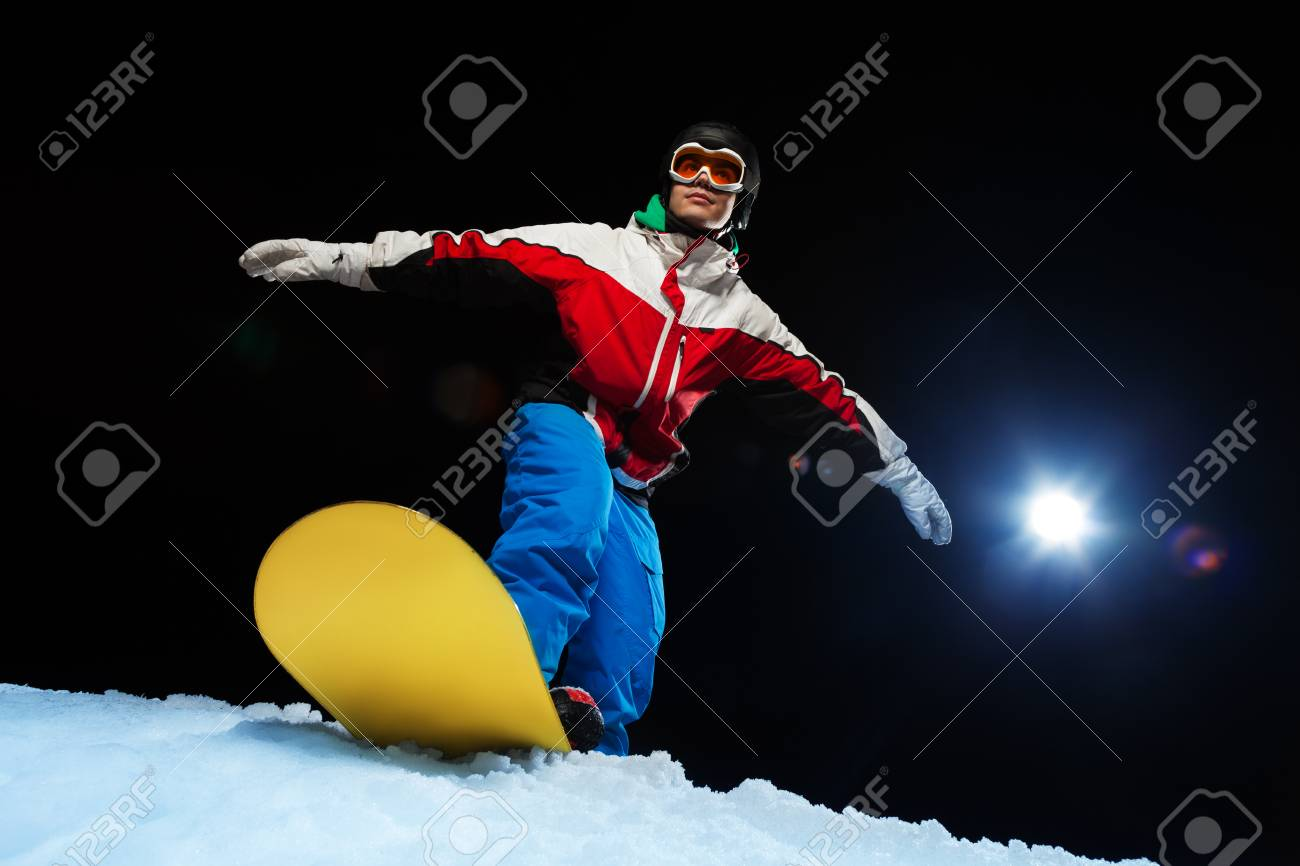 7a20ae7521bf Portrait of young snowboarder wearing ski mask ready to slide from mountain  and balancing on the
