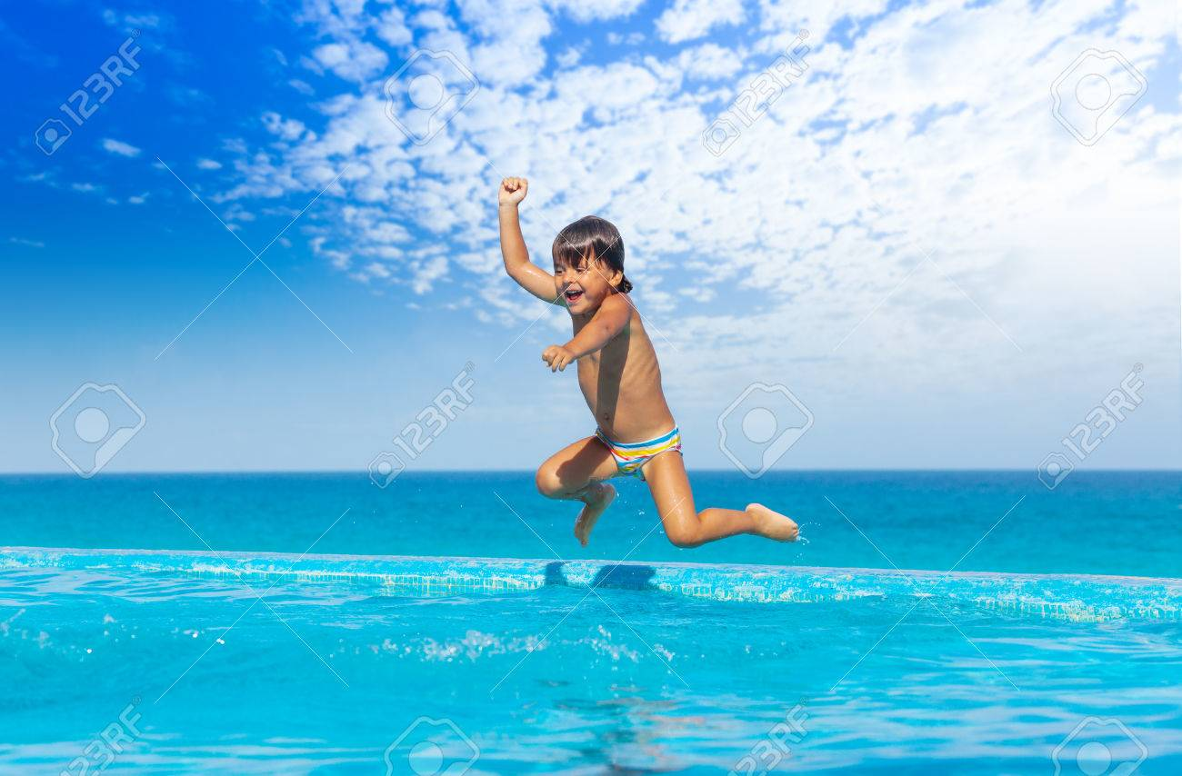 Boy Jumps In Swimming Pool With Seaside Background Stock Photo ...