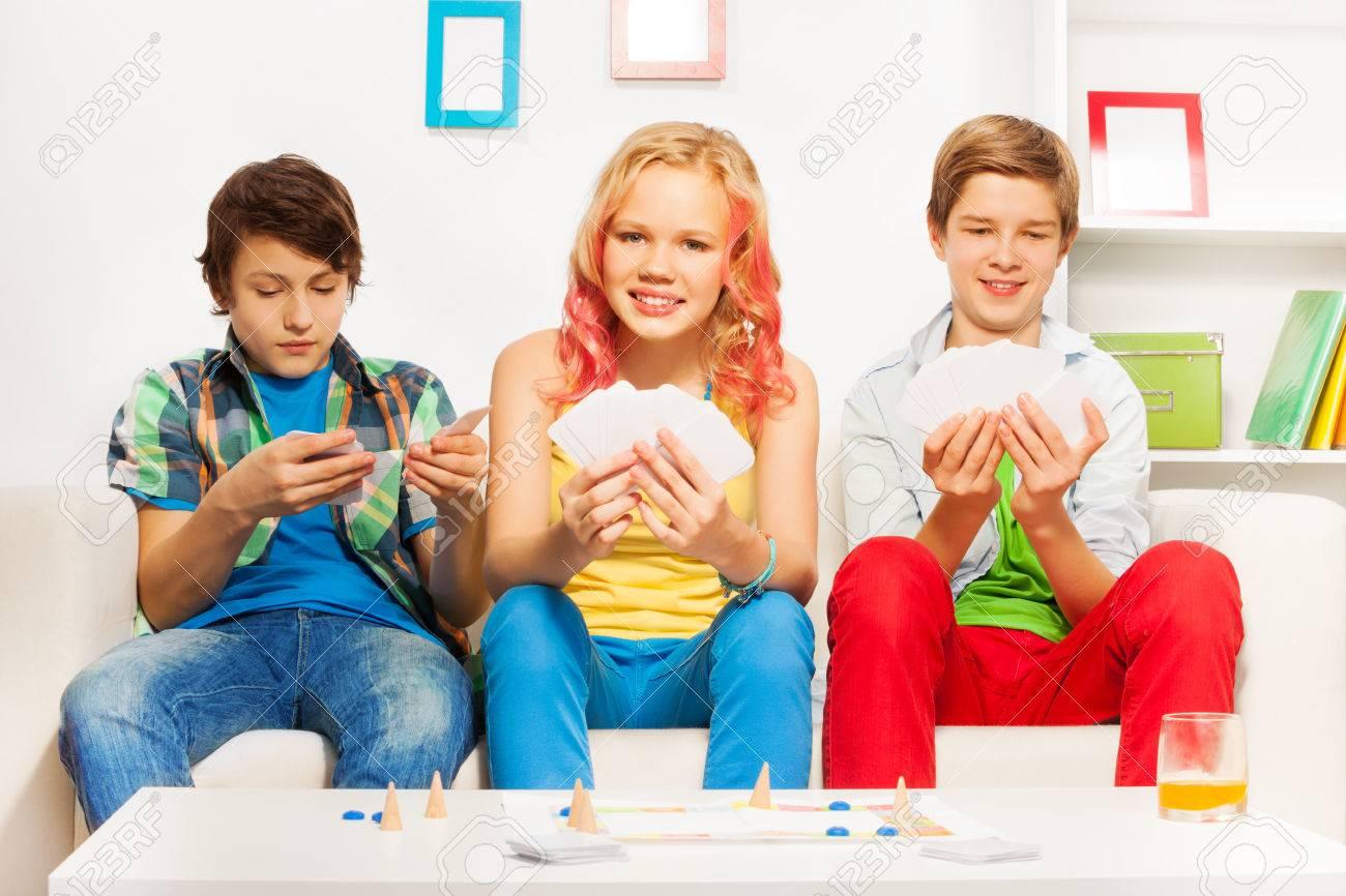 Tres Adolescentes Que Juegan Al Juego De Mesa En El Sofa Blanco