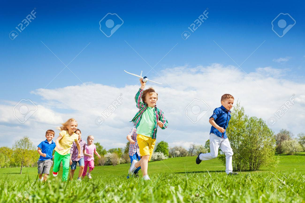 running boy with airplane toy and other children running happily