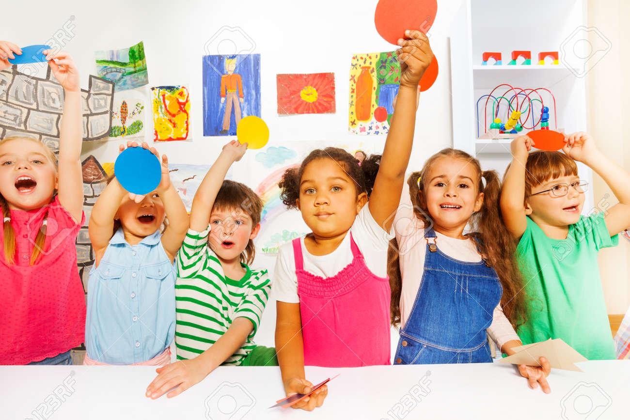 Gruppe des glücklichen jungen und mädchen im kindergarten hält