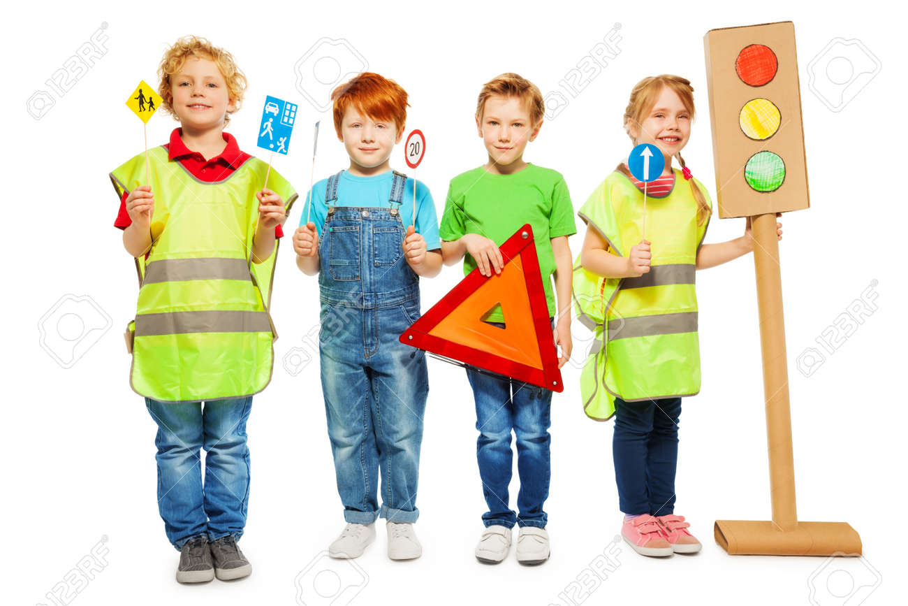 Four kids in high visibility jackets standing in a row, holding warning triangle, road signs and light-signal models, isolated on white - 62152410