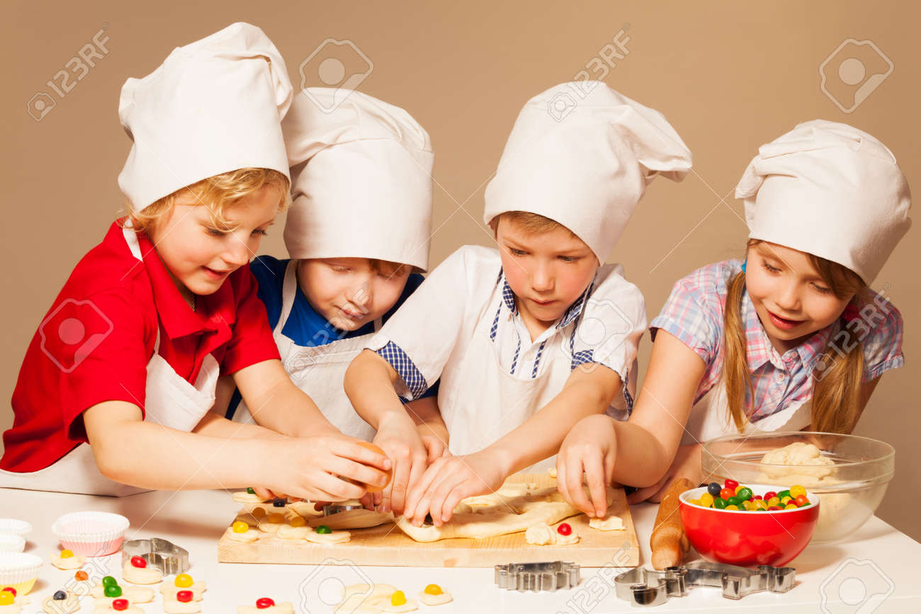 Four cute bakers, boys and girl in cook's uniform having fun making candy filled cookies - 62152498