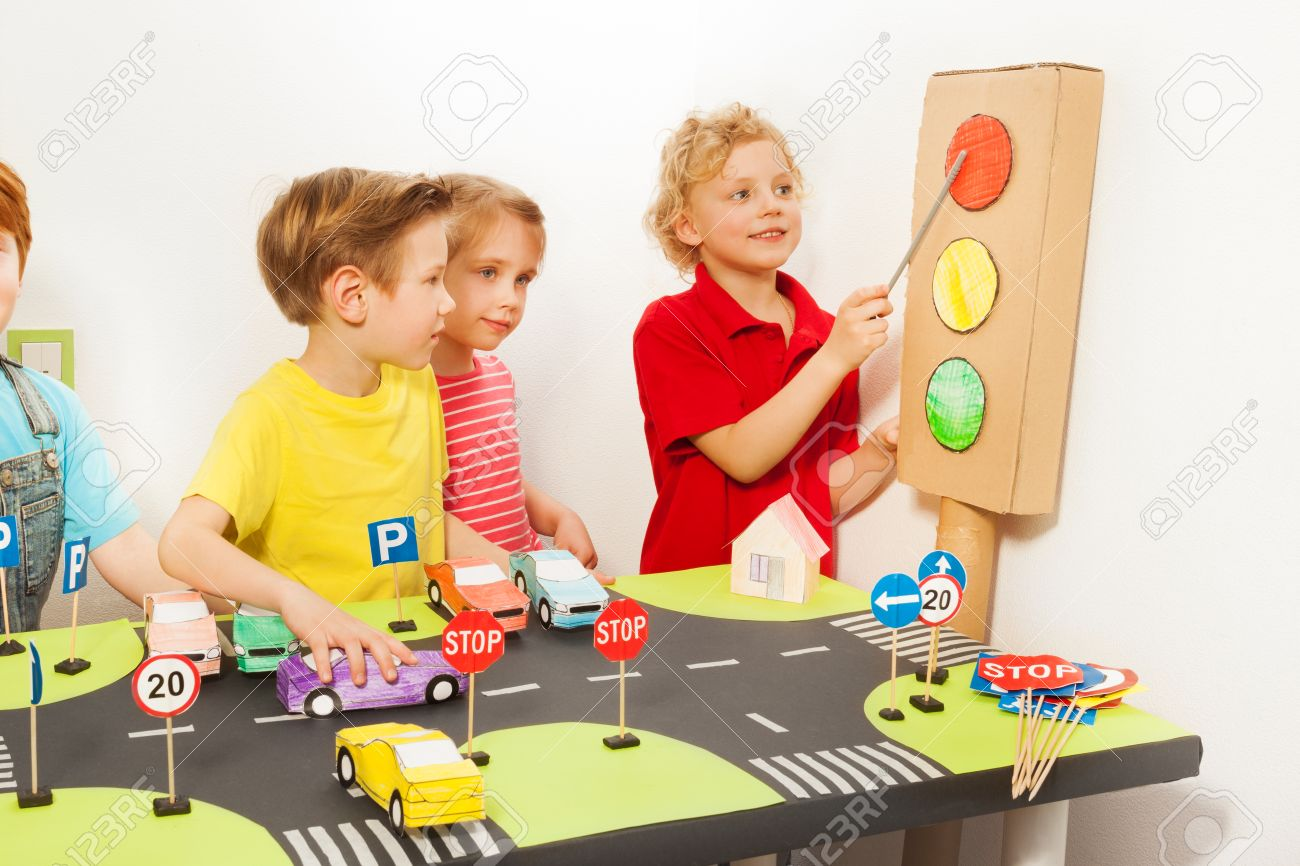 道路運動場で手作りダン ボール信号機、おもちゃの車と道路標識を持つ ...