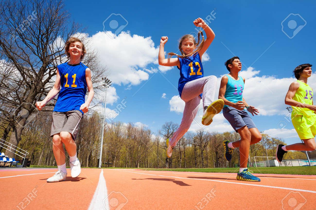 Four happy teenage athletes running on the stadium, bottom view - 60507490