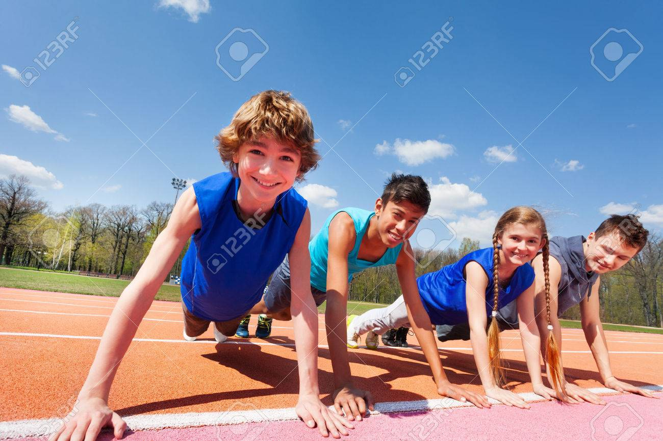 Close-up picture of four happy teenagers in sportswear holding a plank standing in a row on the track outdoors - 60507558