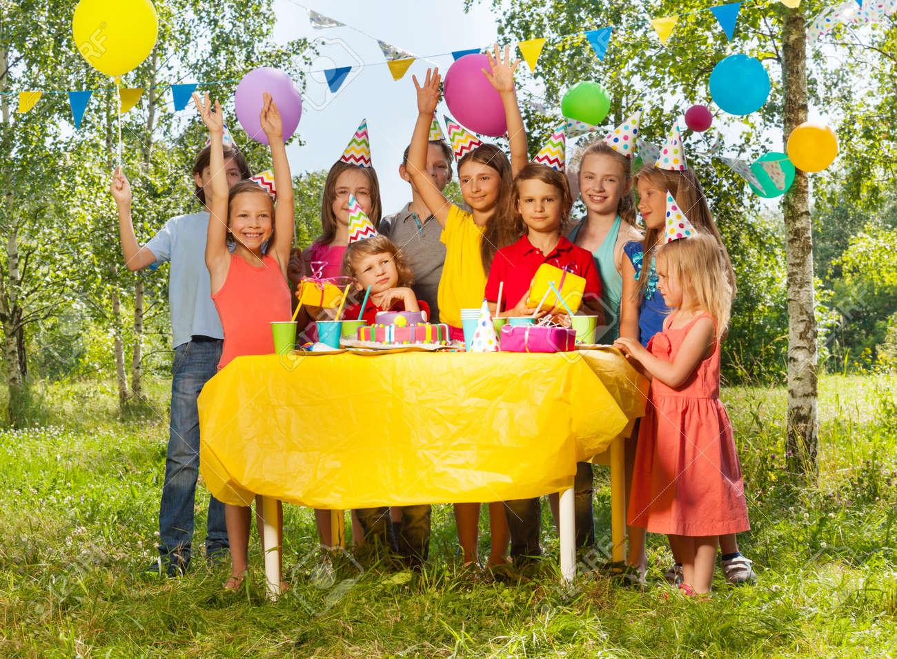 Tavolo Compleanno Bambina : Gruppo di bambini felici età diversa in piedi accanto al tavolo con